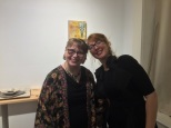 "Elizabeth M. Willey and Ruth Reese, artist, and owner of Reese Gallery, in front of ""Pocket Full of Posies"", which is encaustic mixed media on panel."