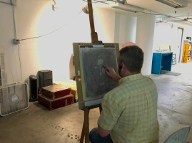 Student erasing out lighter areas of the composition